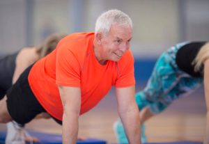 A group of adults are taking a fitness class together at the gym. They are working out on exercise mats and are holding a high plank.